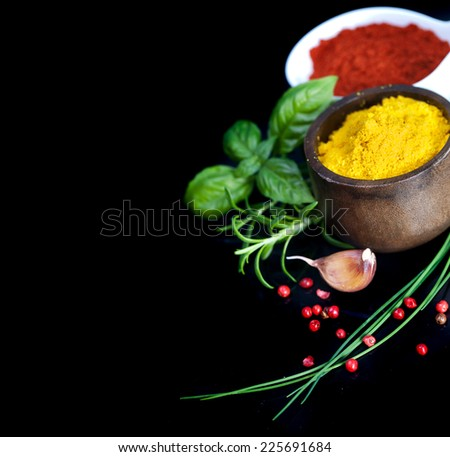 Assorted spices on black background - stock photo