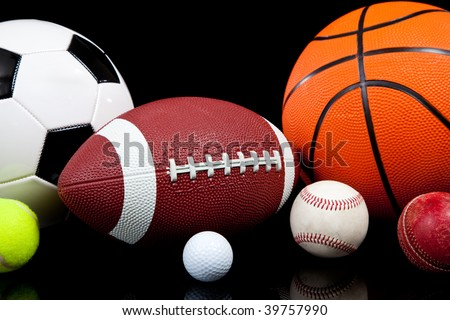 Assorted sports balls including a basketball, american football, soccer ball, tennis ball, baseball, golf ball and cricket ball on a black background