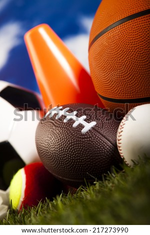 Assorted sports equipment and grass - stock photo