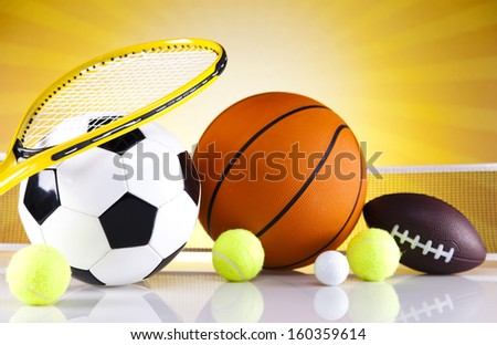 Assorted sports equipment and sunset - stock photo