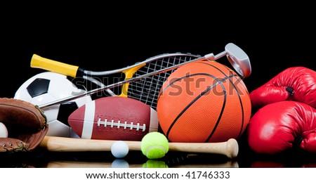 Assorted sports equipment including a basketball, soccer ball, tennis ball, golf ball, bat tennis racket, boxing gloves, football, golf and baseball glove - stock photo