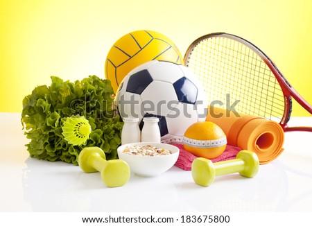 Assorted sports equipment including a basketball, soccer ball, tennis ball, tennis racket and yoga mat.  - stock photo