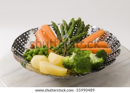 Assorted steamed vegetables in a steamer. White background.