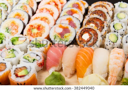 Assorted sushi rolls on a wooden board - stock photo