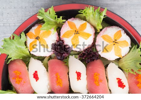 Assorted sushi, tamari and maki in a nice tray on wooden table - stock photo