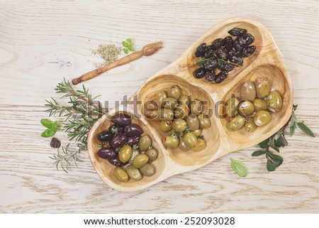 Assorted types of olives. Variety of green, black and mixed marinated olives in olive tree dish on wooden table  - stock photo