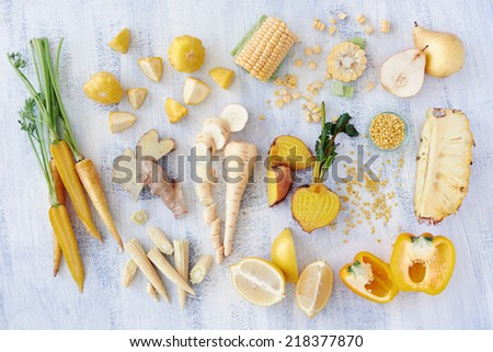 Assorted types of yellow hued fruits and vegetables shot overhead, carrot corn lemon pineapple pear parsnip bell pepper capsicum golden beetroot, part of a color spectrum collection - stock photo