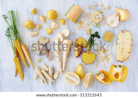 Assorted types of yellow hued fruits and vegetables shot overhead, carrot corn lemon pineapple pear parsnip bell pepper capsicum golden beetroot, part of a color spectrum collection