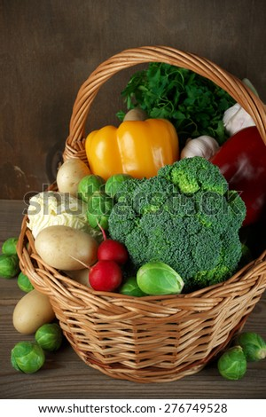 Assorted vegetables in basket on rustic wooden background. - stock photo