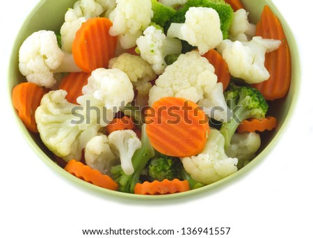 Assorted vegetables in green bowl isolated on white closeup