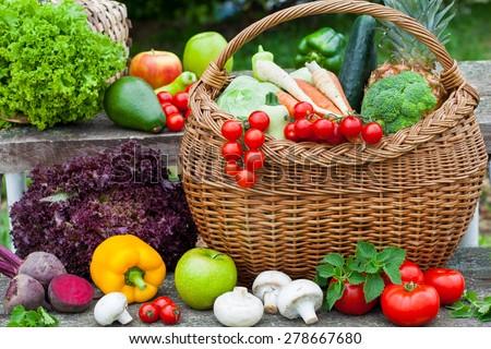 Assorted vegetables in wicker basket in the garden - stock photo