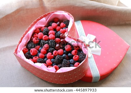 assorted wild berries in gift red box in the shape of heart