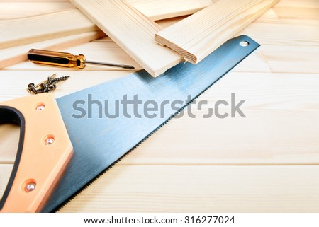 Assorted work tools on wooden background - stock photo