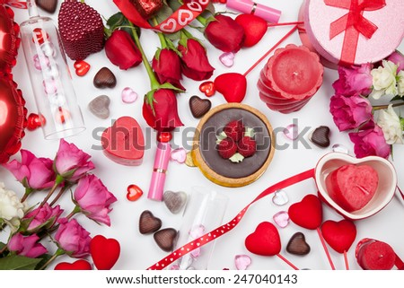 Assortiment of different Valentine Day gifts, candies, red roses, cosmetics, candles, and bottle of Champagne.