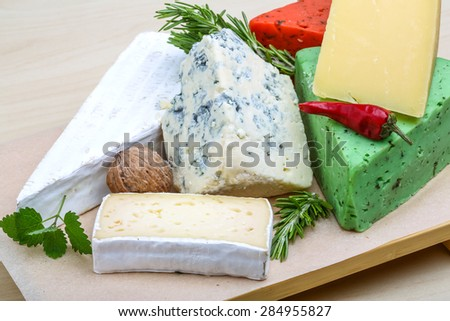 Assortment cheese with herbs on the wood background