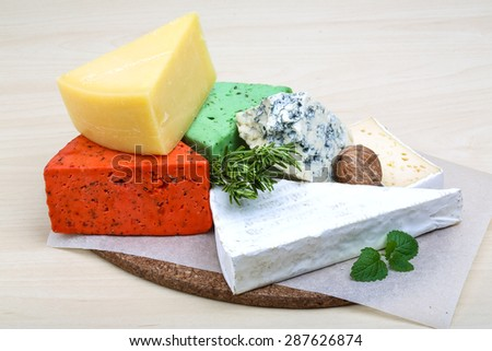 Assortment cheese with herbs on the wood background - stock photo
