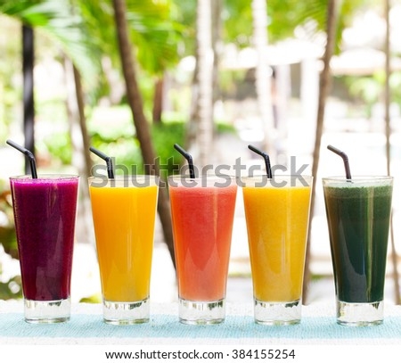 Assortment juices, smoothies, beverages, drinks variety on a outdoor tropical background Copy space - stock photo