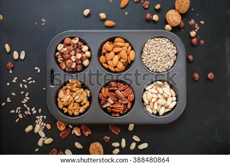Assortment Nuts in Pastry Mold Peanut Almond Walnut Filbert Hazel Nut Sunflower Pecan Black Wooden Background Scattered Top view Healthy Concept - stock photo