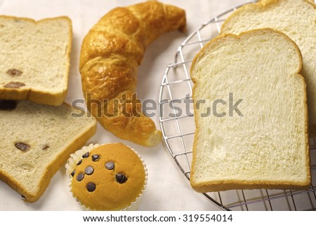 assortment of baked bread and rolls arranged on coarse textured, woven fabric