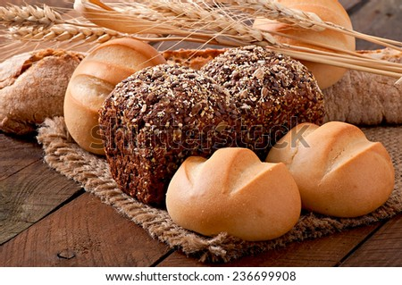 Assortment of baked bread on a wooden table - stock photo