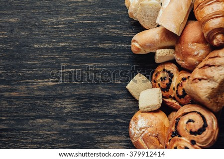 assortment of baked bread on dark wood table. Top view with copy space - stock photo