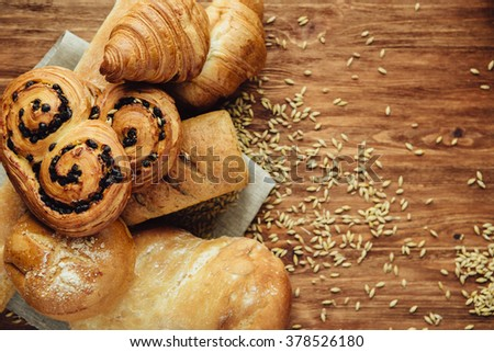 assortment of baked bread on linen napkin on the wood table. Top view with copy space - stock photo