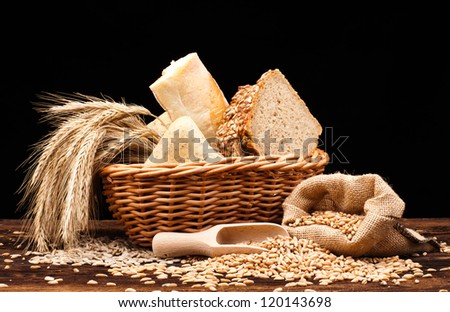 assortment of baked bread on wood table and black background - stock photo