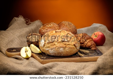 Assortment of baked bread with wheat and apples arranged on coarse textured woven fabric - stock photo