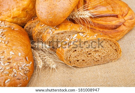 Assortment of baked breads with spikelets of wheat on burlap fabric