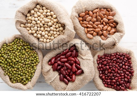 Assortment of beans and lentils in hemp sack on wooden background. green bean, groundnut, soybean, red kidney bean , black bean ,red bean and brown pinto beans