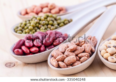 Assortment of beans and lentils in wooden spoon on wooden background. mung bean, groundnut, soybean, red kidney bean , black bean ,red bean and brown pinto beans .