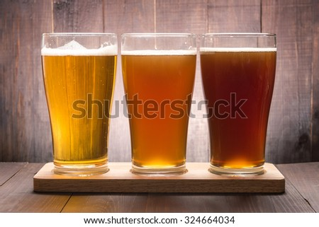 Assortment of beer glasses on a wooden table. - stock photo