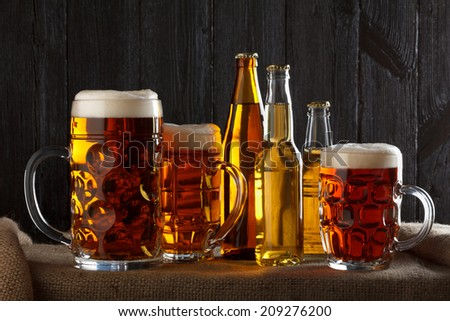Assortment of beer glasses on table with burlap cloth, dark wooden background - stock photo