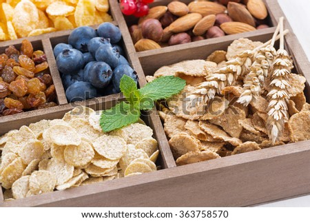 assortment of breakfast cereal, dried fruit, berries and nuts in a wooden box, closeup, horizontal - stock photo