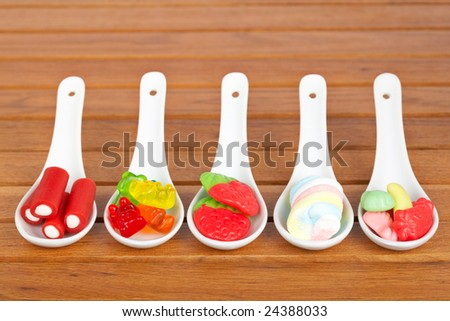 Assortment of candies in the spoons with soft shadow in the wooden background - stock photo