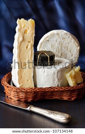 Assortment of cheese in a wicker basket. - stock photo
