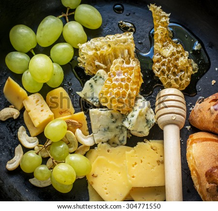Assortment of cheese with fruits, berries, honey and nuts on wooden table, selective focus - stock photo