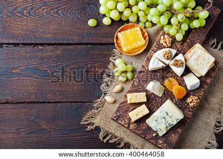 Assortment of cheese with honey, nuts and grape on a rustic cutting board wooden background - stock photo