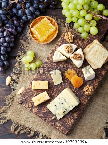 Assortment of cheese with honey, nuts and grape on a rustic cutting board wooden background Toning  - stock photo