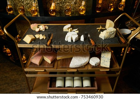 Assortment of cheeses, aged parmesan, gorgonzola, ricotta, taleggio, pecorino and brie cheese on cutting board