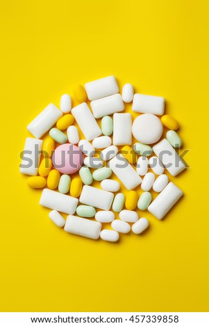 Assortment of chewing gums, mint candies and drops on bright yellow background. Lying in circle. - stock photo