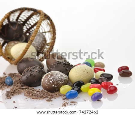 assortment of chocolate eggs , candies and  a basket, close up - stock photo