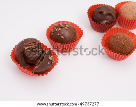 assortment of chocolate truffles isolated on white, focus on truffle in foreground, copy space at right - stock photo