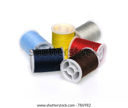 Assortment of colored spools of thread over white