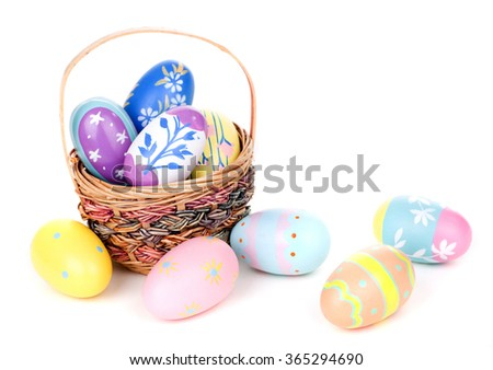 Assortment of colorful Easter eggs and basket on a white background