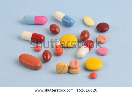 assortment of colorful pills and capsules isolated in blue background - stock photo