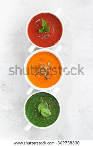 assortment of colorful vegetable cream soup on a white background, top view, vertical - stock photo