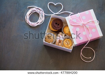 Assortment of cookies with gift box on a grey wooden table