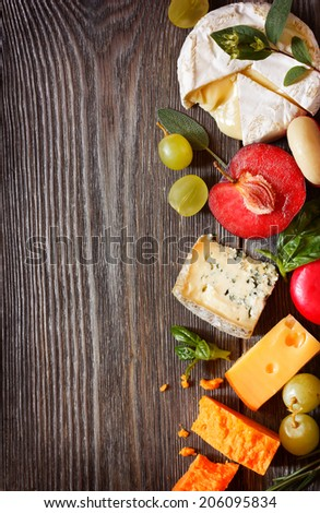 Assortment of delicious cheeses and fruit on a wooden background with copy space for text. - stock photo
