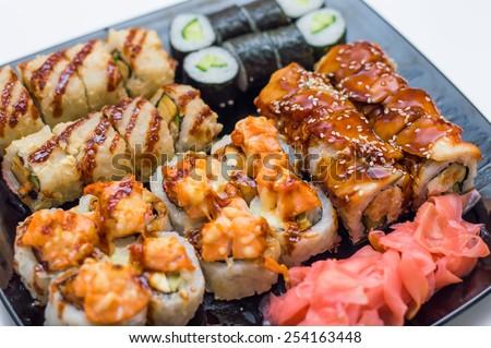 Assortment of delicious fresh, tempura and baked sushi maki with salmon, eel, cucumber, avocado, scrambled eggs, shrimp and unagi sauce - stock photo
